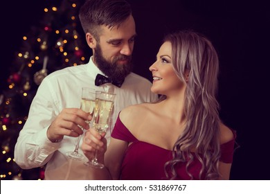 Couple in love having a midnight toast with glasses of champagne on a Christmas celebration