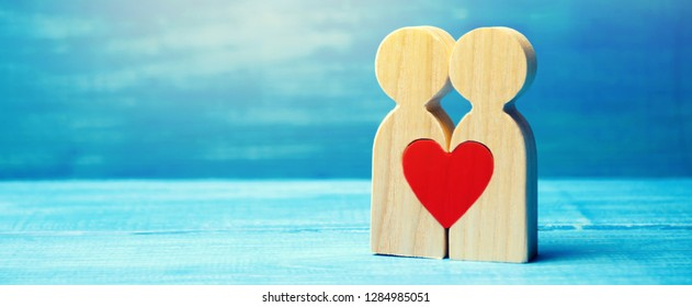 A couple in love and a heart between them. The concept of love and sympathy between two people. Meeting the love of all life. Human happiness. Dating. Declaration of Love. Valentine's Day. Minimalism