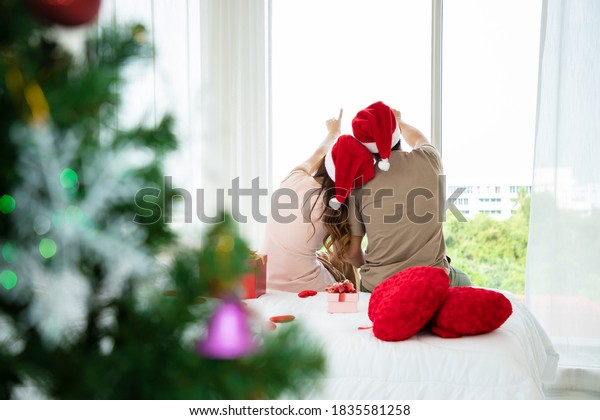 A couple love hepls decorate christmas tree and select variety of gifts at this Christmas party tonight in bedroom. They are looks happy and has a bright smile.  Gifts for important people. Holiday