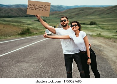 A couple in love hitchhiking. A young couple votes on the road. Travel on your own. Man and woman are hitchhiking. Couple Standing near Road. Man and woman catch a car on the road