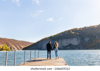 the couple in love hold hands and admire the view. back view. river and cliff