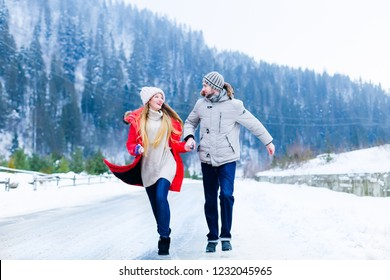 the couple in love hold hands and look at each other while running on a mountain winter road