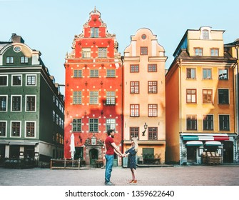 Couple in love holding hands together in Stockholm during a romantic date walk.  Summer vacations lifestyle Stortorget architecture colorful houses Sweden landmarks