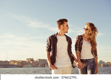 Couple in love holding hands and walking on the beach