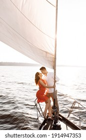 Couple in love holding on to a white sail and kissing on a yacht in the blue sea . High quality photo