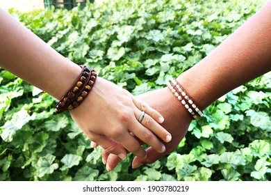 couple in love holding white and black hands of teenagers in bracelets on large green tropical background