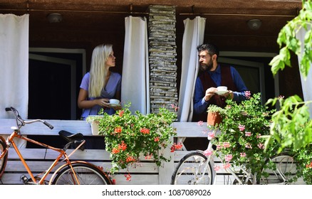 Couple in love holds cups of coffee outside.