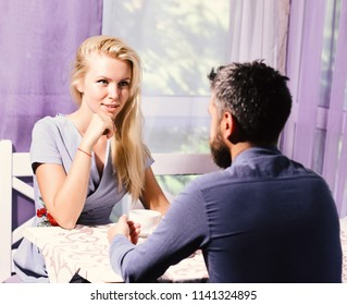 Couple in love holds cups of coffee at table. Woman and flirty face and man have an affair. Girl with blond hair and bearded guy on light cafe background. Lunch time and communication concept.