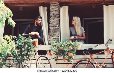 Couple in love holds cups of coffee outside. Lunch time and romance concept. Girl with blond hair and bearded guy on cafe background. Woman and man with flirty faces have a date on terrace with bikes