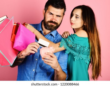 Couple in love holds shopping bags on pink background. Money and shopping concept. Man with beard holds credit card and piggy bank. Guy with beard and girl with sly faces do shopping.