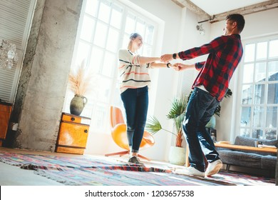 Couple in love at home. Spending happy time and dancing in the big spacious room, laughting and hugging. Bright loft apartment