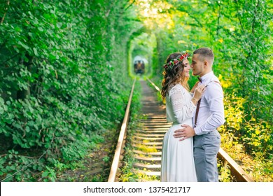 couple in love hug and look at each other. Tunnel of love with trees and railway