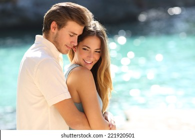 Couple in love hugging on a tropical beach with a turquoise water in the background