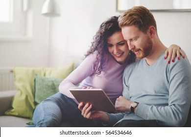 Couple in love hugging and smiling at home