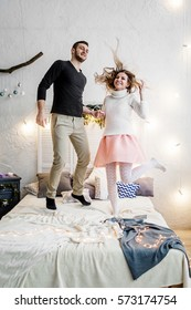 Couple in love jumping in the bedroom on new years eve or st vilentine's day in winter