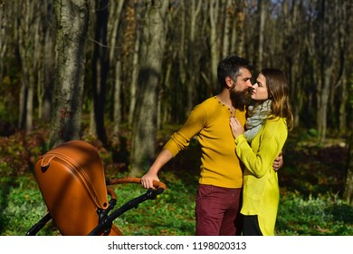 Couple in love kiss in pleasure park. Happy family with baby pram spend time with pleasure together. True love is a big deal.