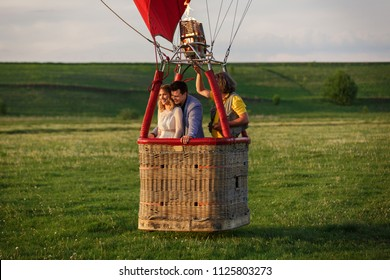 A couple in love kisses in balloon basket. Romantic travel and honeymoon concept