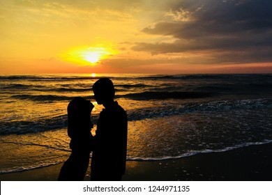 A couple in love are kissing against the sunset on the beach. Silhouettes of man and woman, sea, waves, sunset sky. Love and romance concept.