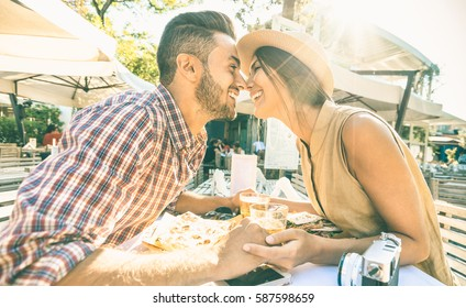 Couple in love kissing at bar eating local delicacie on travel excursion - Young happy tourists enjoying moment at street food restaurant - Relationship concept with lovers at first date - Warm filter
