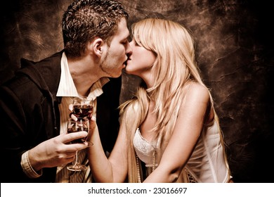 couple in love, kissing and holding glasses with wine