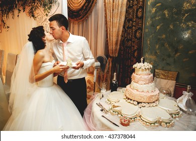 Couple in love kissing near wedding cake