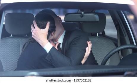 Couple in love kissing passionately in auto, romantic date, secret affair