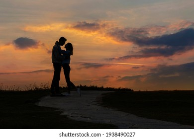Couple in love kissing at sunset. Silhouette of two people on a background of beautiful evening sky.