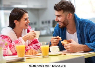 Couple in love in the kitchen having breakfast together