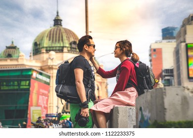 Couple in love, a lady backpackers smiling touching a man backpacker in front of Flinder train station in Melbourne, 11/05/18