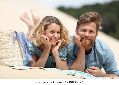 couple in love laying on the sand on a beach