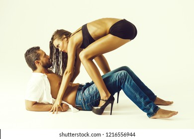 couple in love looking at each other with passion. Sexi girl or cute woman with long hair in erotic, black bra, shorts, high heel shoes and bearded man or macho lying on floor isolated on white