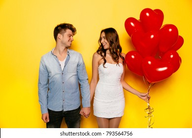 Couple in love looking to each other, holding hands together, dressed in jeans shirt, white dress, standing with red balloons on yellow background, celebrating Valentine's day
