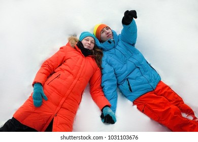 Couple in love is lying on snow and looking to the sky. Romantic walking in snowy winter park.