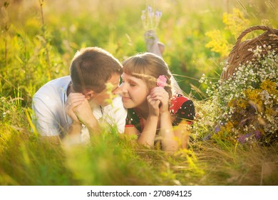couple in love lying in spring meadow. man ad woman face to face. loving people. picnic. happy smiling couple in love