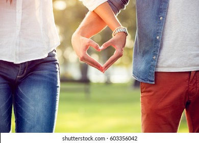 Couple in love making heart with hands