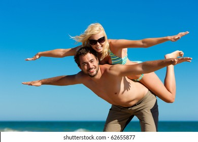 Couple in love - man carrying his wife on the back on a beach vacation, they are feeling visibly free and happy