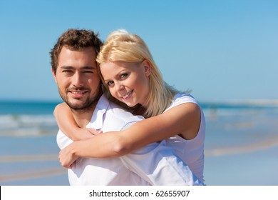Couple in love - man having his woman piggyback on his back under a blue sky on a beach
