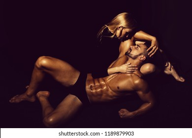 couple in love of man with muscular wet body and strong athletic torso with sexy blonde girl in underwear pants on black background, love relations