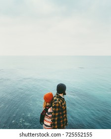 Couple in love Man and Woman back to back standing above sea Traveling together happy emotions Lifestyle concept. Young family romantic vacations journey