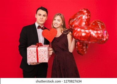 Couple in love, man and woman give each other gifts, holding gift boxes and balloons, on a red background, Valentine's Day