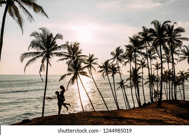 A couple in love meets a sunset on the sea among the palm trees. Man and woman at sunset. Honeymoon on the Islands. Man and woman meet sunset. Happy loving couple. Silhouette lovers. Wedding travel