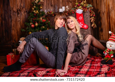 couple in love on the background of new year and christmas lights near the burning fireplace
