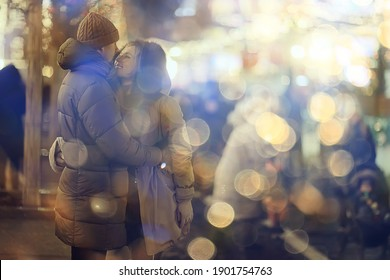 couple in love on a christmas walk in the city, evening snowfall december holiday new year