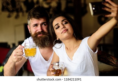 Couple in love on date drinks beer. Man bearded hipster and girl with beer glass full of craft beer. Best friends or lovers drinking beer in pub. Take selfie photo to remember great date in pub.