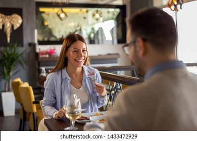 Couple in love on a date, sitting at a restaurant table, having lunch, drinking wine and enjoying each others company