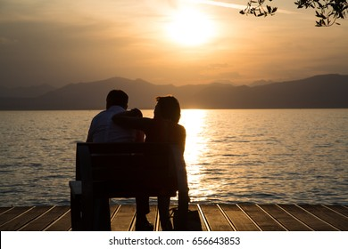 Couple in love on a park bench at Lake Garda