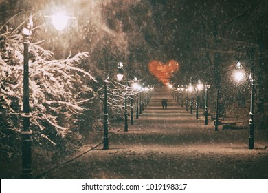 Couple in love on a romantic date walks through the snowy night winter park alley with beautiful lanterns covered with snow to the red heart formed by tree branches on St Valentine day.
