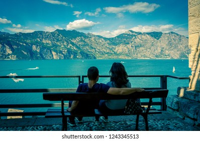 Couple in love on the shores of Garda lake, Malcesine on Garda lake, Italy. In love couple on the waterfront. photo in style lomography.