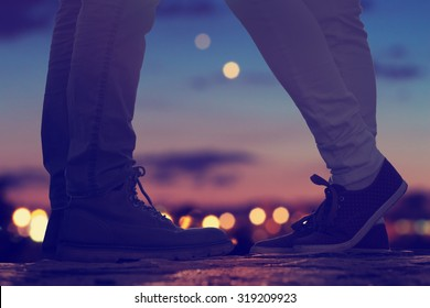 Couple in love on the street with defocused city lights and traffic.