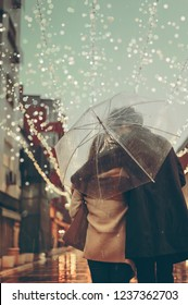 Couple in love on the street on a rainy day. Friends walking down the street looking in same direction under transparent umbrella